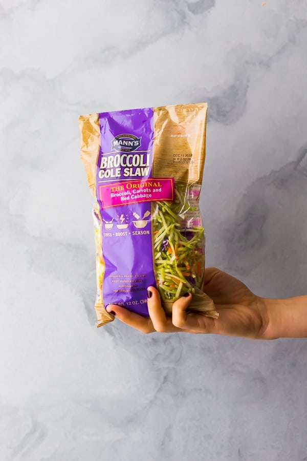 a hand holding the broccoli cole slaw for the egg roll in a bowl recipe