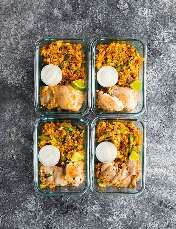 overhead shot of four glass meal prep containers with indian chicken