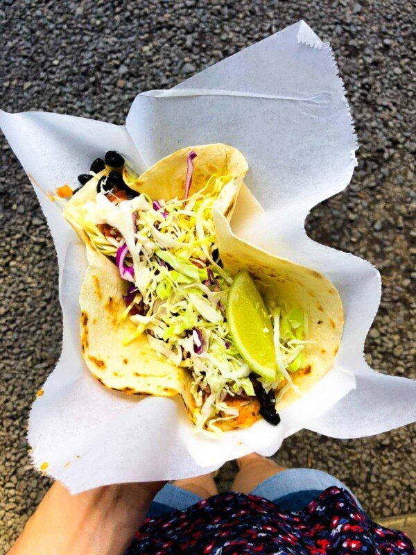 overhead shot of a hand holding up a large taco