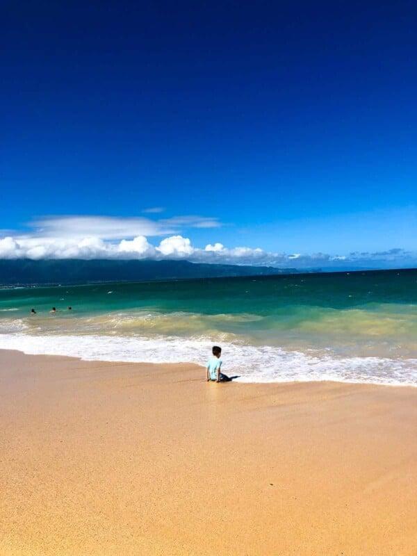a boy sitting on the beach in maui