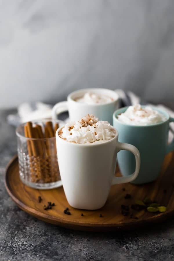 three cups of chai tea latte and a cup of cinnamon sticks on wood tray