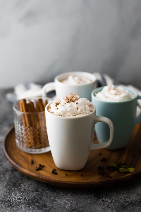 chai tea latte in coffee mugs on wooden serving tray