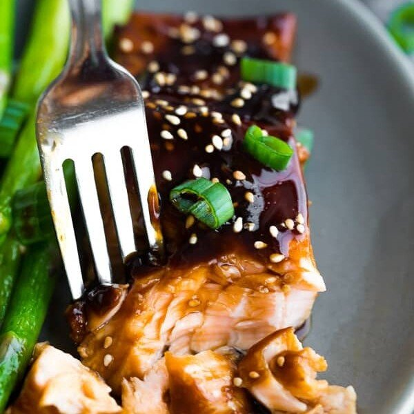 Close up shot of a fork taking off a piece of teriyaki salmon with green beans next to it