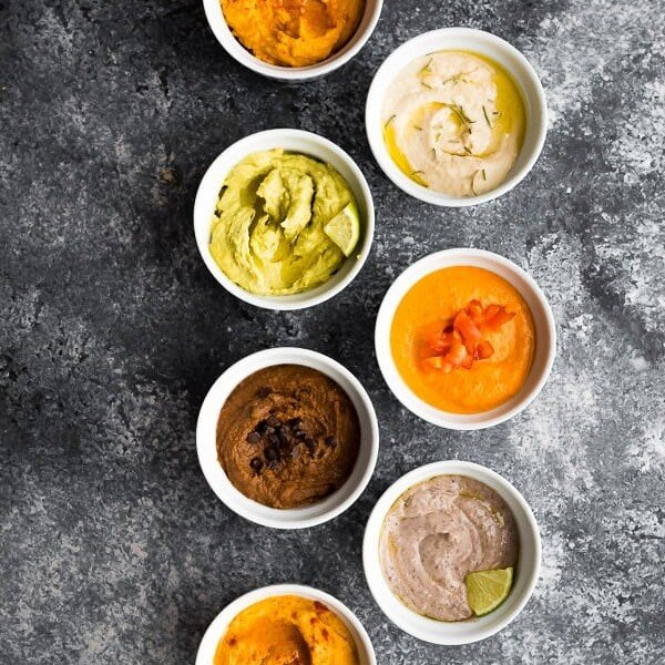 overhead shot of 7 different hummus recipes in white bowls