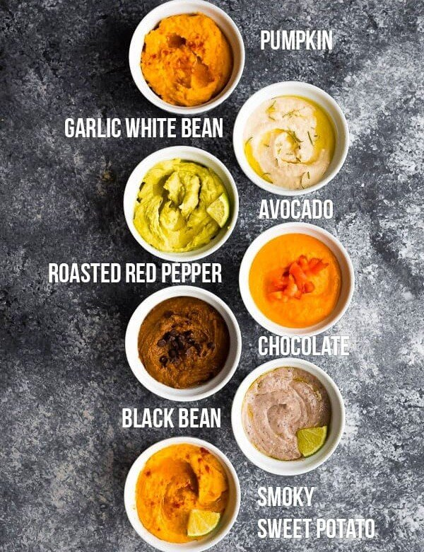 overhead shot of 7 different hummus recipes in white bowls with labels