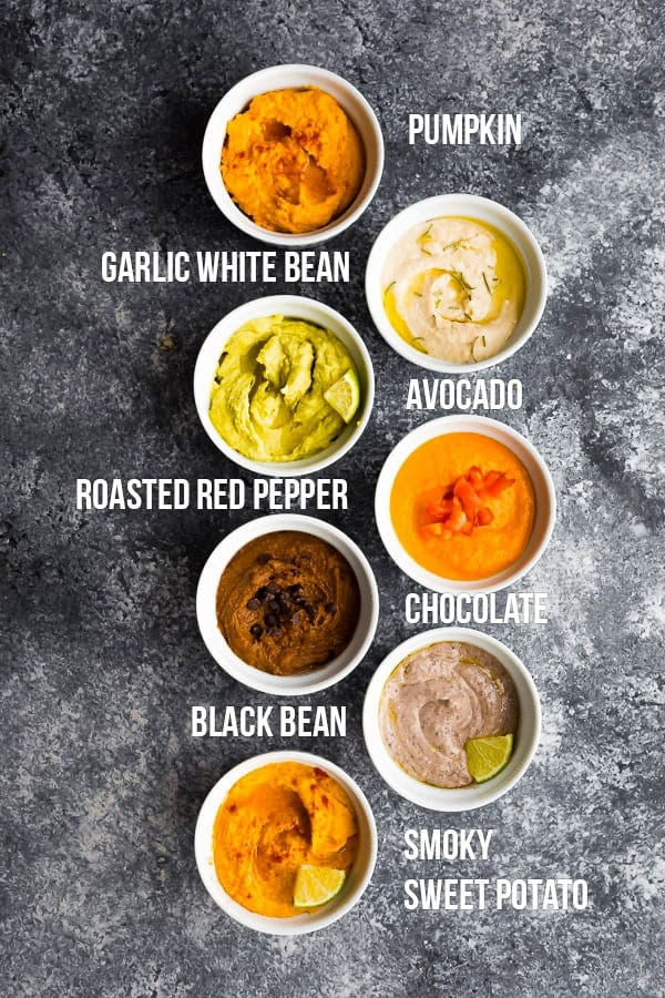 overhead view of 7 hummus recipe flavors in white ramekins