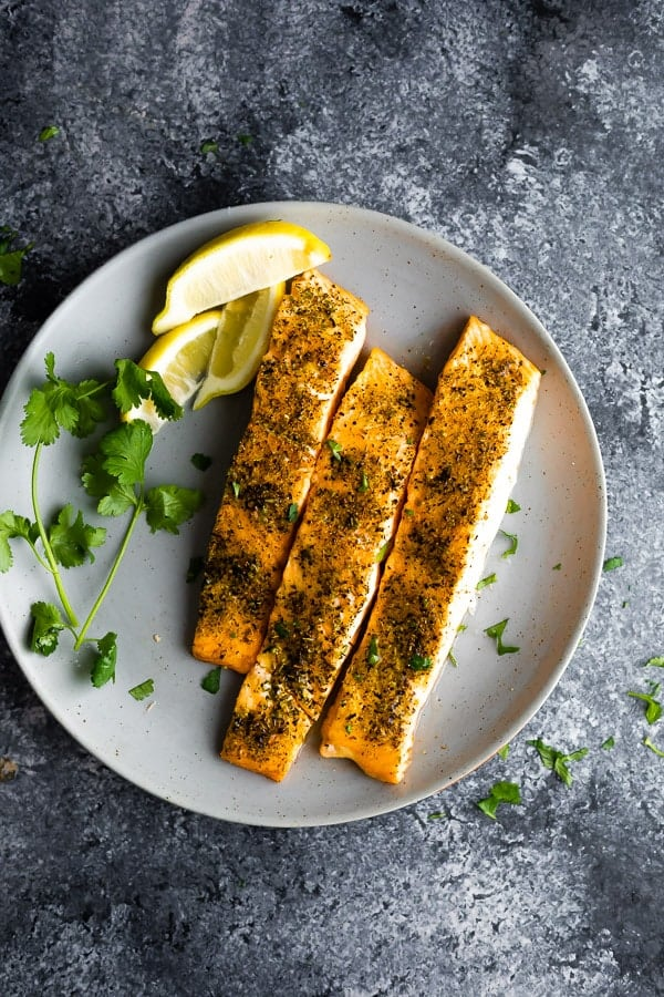 how long to cook salmon in the oven depends on size and thickness- showing 6 oz cooked salmon fillets on a plate
