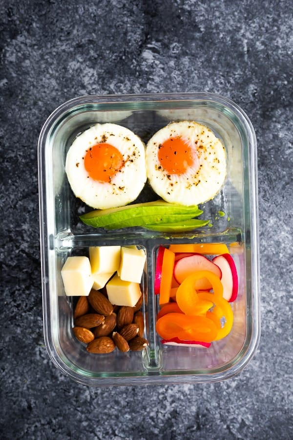 baked egg cups in bento box with avocado, cheese, almonds and vegetables
