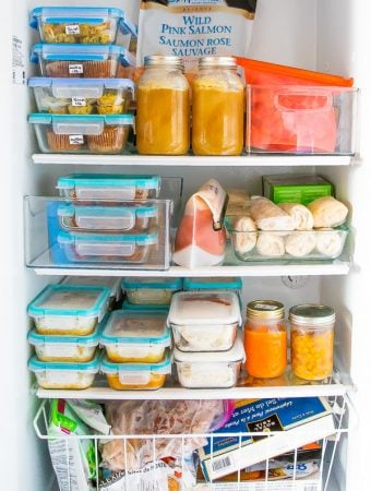 An open freezer filled with food prep containers and meals