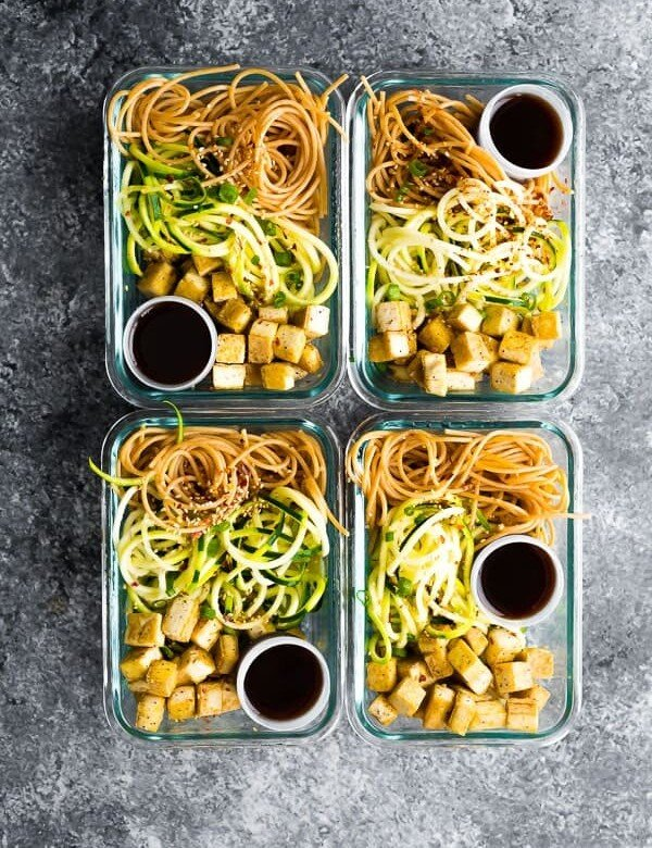 overhead shot of four spicy tofu noodle meal prep bowls in glass containers