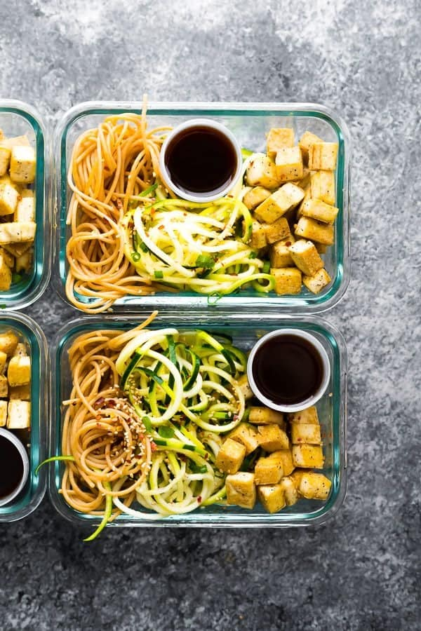 overhead shot of two glass meal prep containers filled with spicy tofu noodles