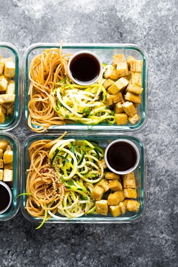 baharatlı tofu erişte ile doldurulmuş iki cam yemek hazırlama kabının üstten görüntüsü