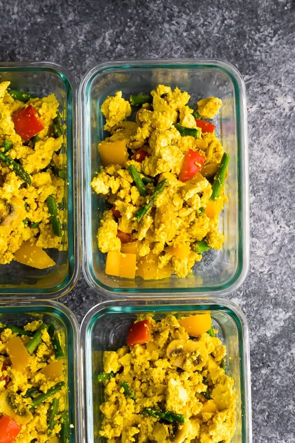 cooked tofu scramble portioned out into meal prep container, on grey surface
