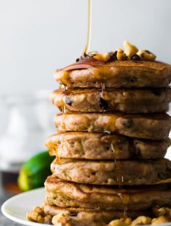 stack of zucchini chocolate chip pancakes with maple syrup being drizzled on top