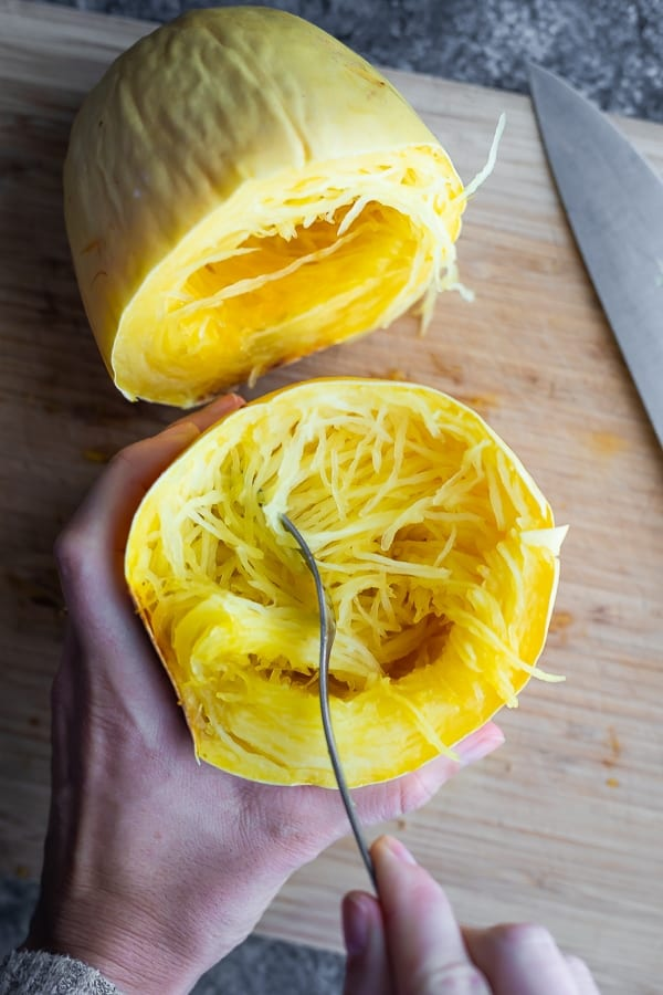 how to cook spaghetti squash whole- last step is pulling the 'noodles' out with a fork