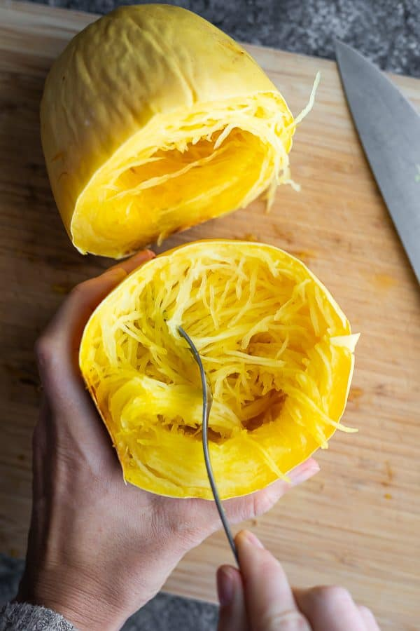 hand holding half a cooked spaghetti squash and scooping out the insides with a fork