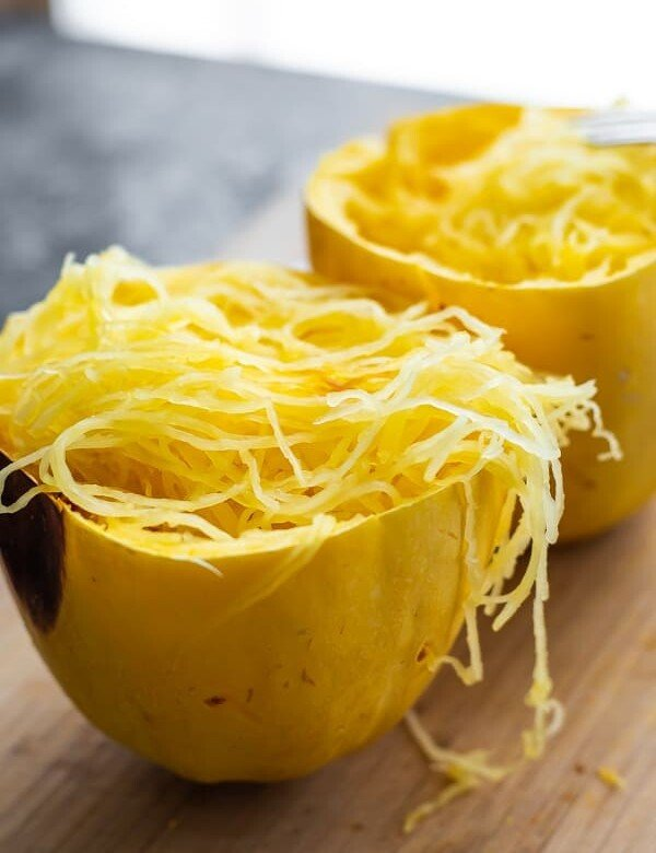 two halves of cooked spaghetti squash sitting on a wood cutting board