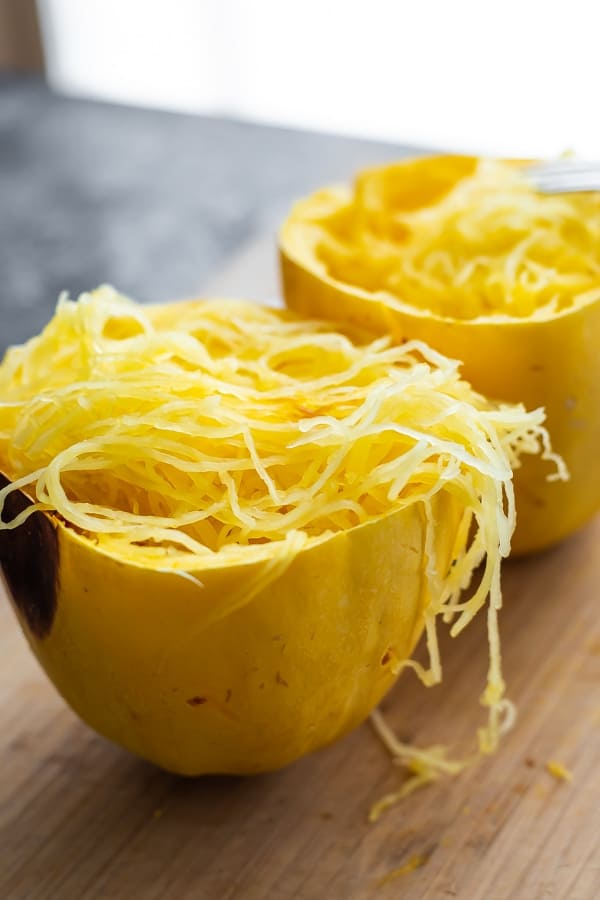 how to cook spaghetti squash- two cooked spaghetti squash halves on a cutting board