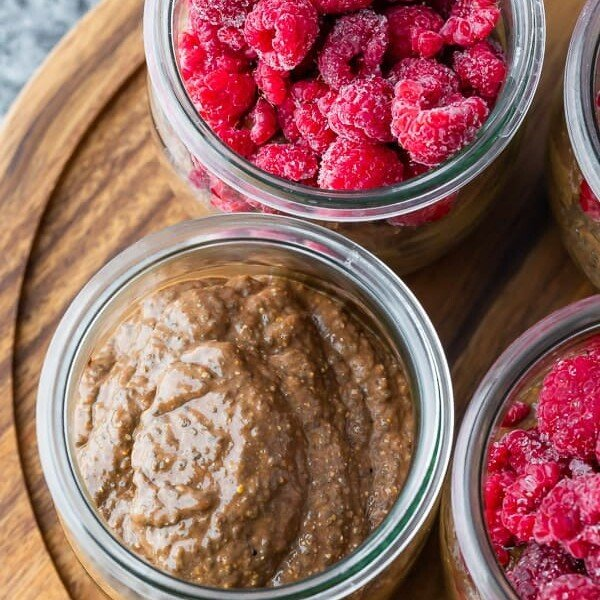 overhead shot of jars filled with chocolate chia pudding and fresh raspberries on wood board