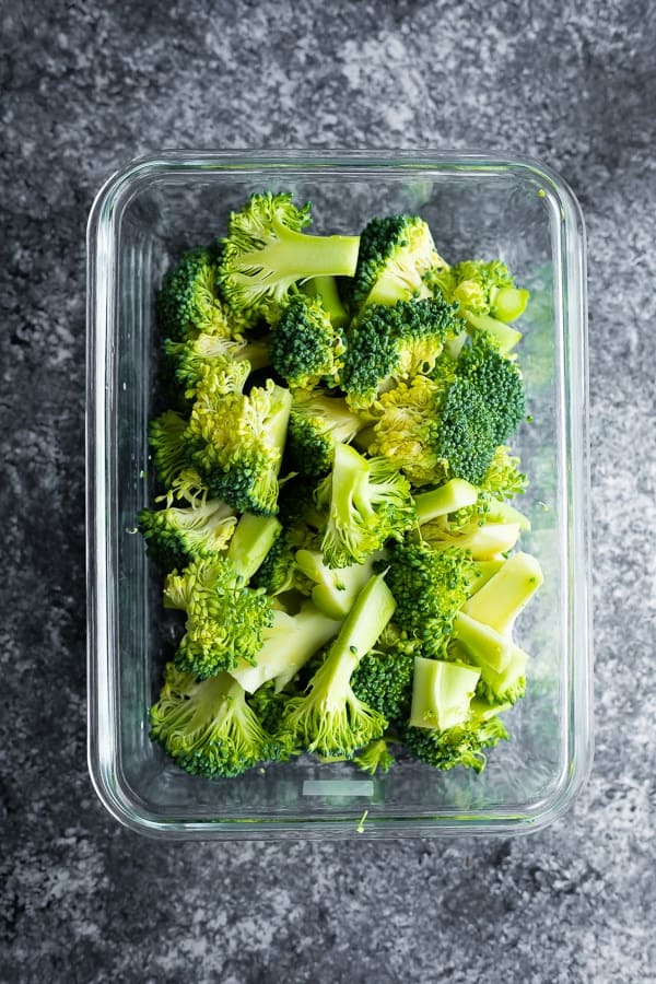how to cook broccoli- showing meal prep container with raw broccoli