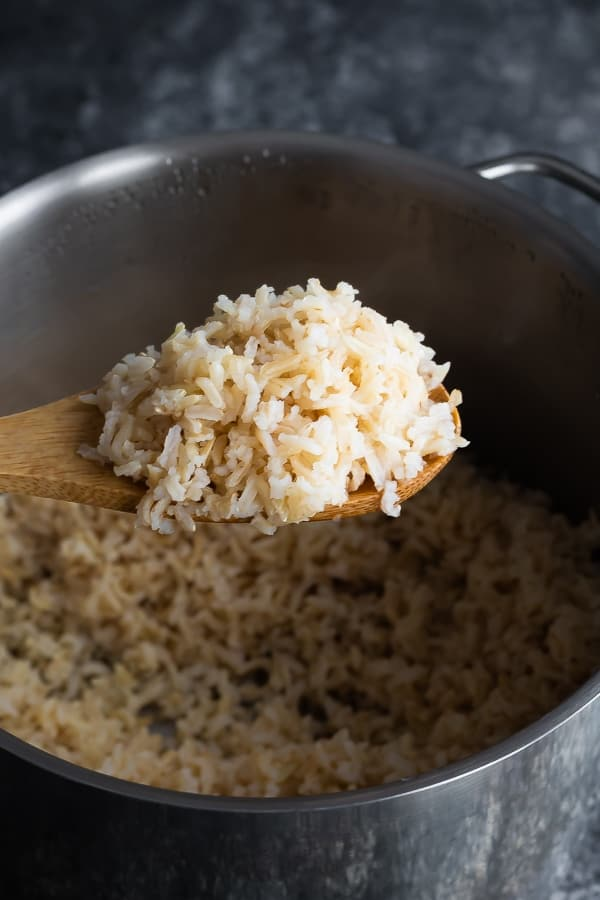 scooping the perfectly cooked brown rice from how to cook brown rice post