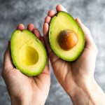 hands holding an avocado cut in half