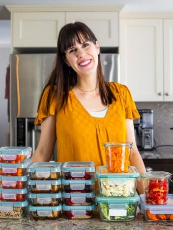 Denise standing at her counter behind stacks of meal prep containers