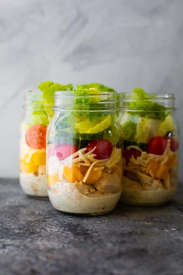 three glass mason jars filled with ranch chicken jar salads