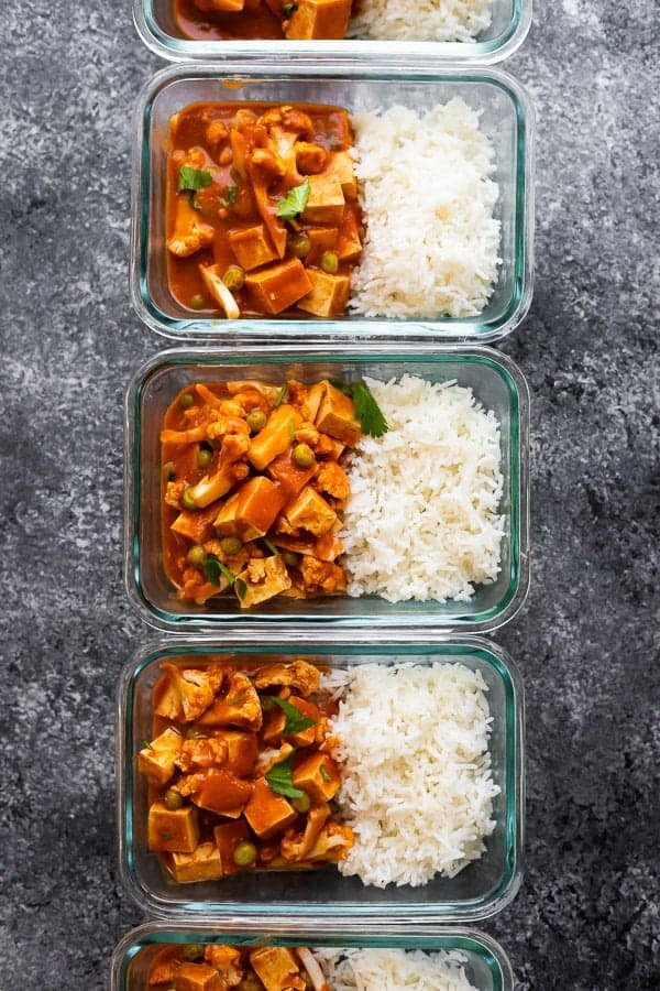 overhead shot of three glass meal prep containers filled with vegan slow cooker tikka masala