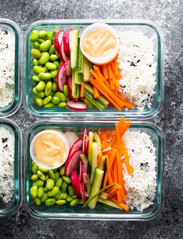 overhead shot of glass meal prep containers filled with vegan sushi bowls
