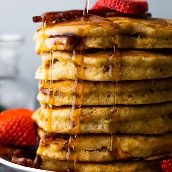 side view of a large stack of bacon pancakes on a plate with syrup being drizzled over and fresh strawberries