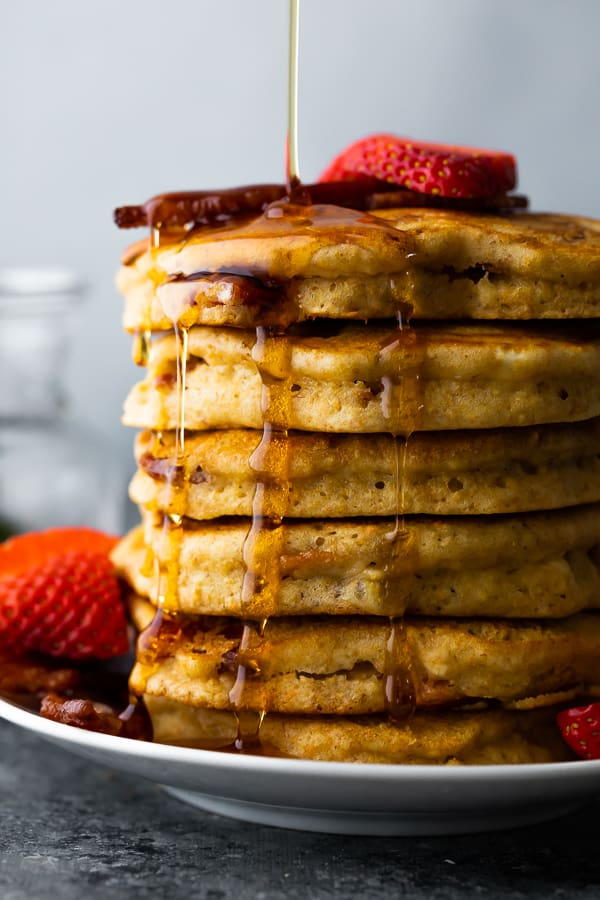 maple syrup drizzling on a stack of bacon pancakes