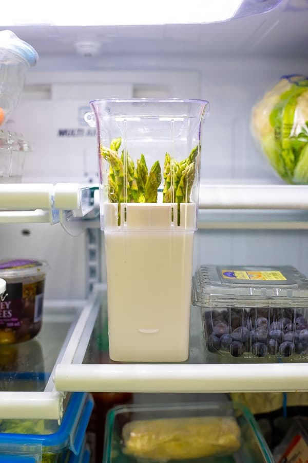 showing how to store asparagus for meal prep in a herb saver