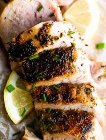 Close up shot of sliced pork tenderloin with fresh lemon slice