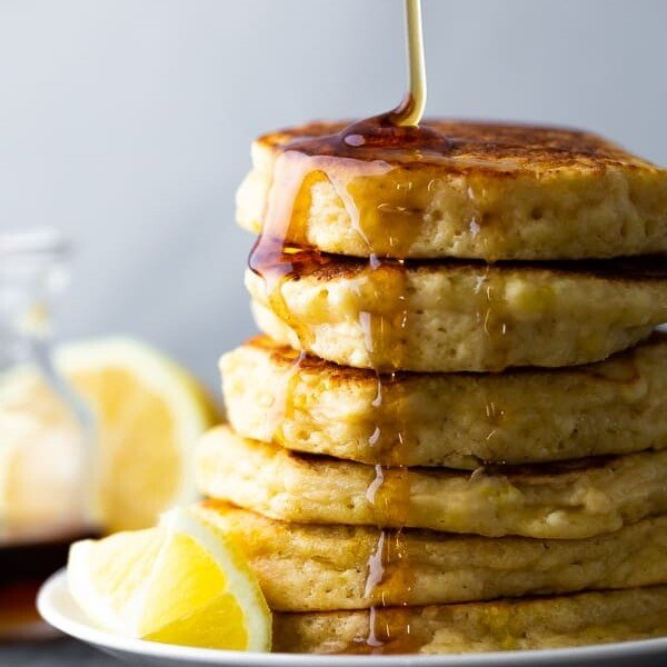 side image of stack of lemon ricotta pancakes with maple syrup drizzled and lemon slices