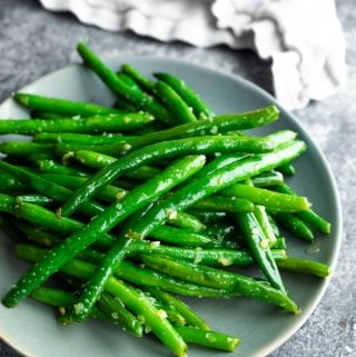Pile of sauteed green beans with garlic butter on gray plate