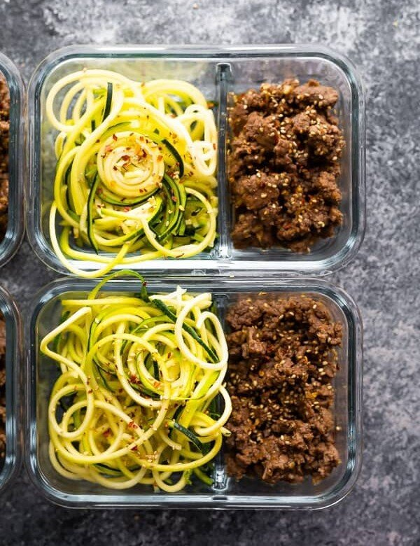 overhead shot of glass meal prep containers filled with sesame ginger beef and zucchini noodles