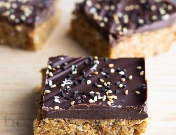 three pieces of chocolate tahini oat bars on wood board