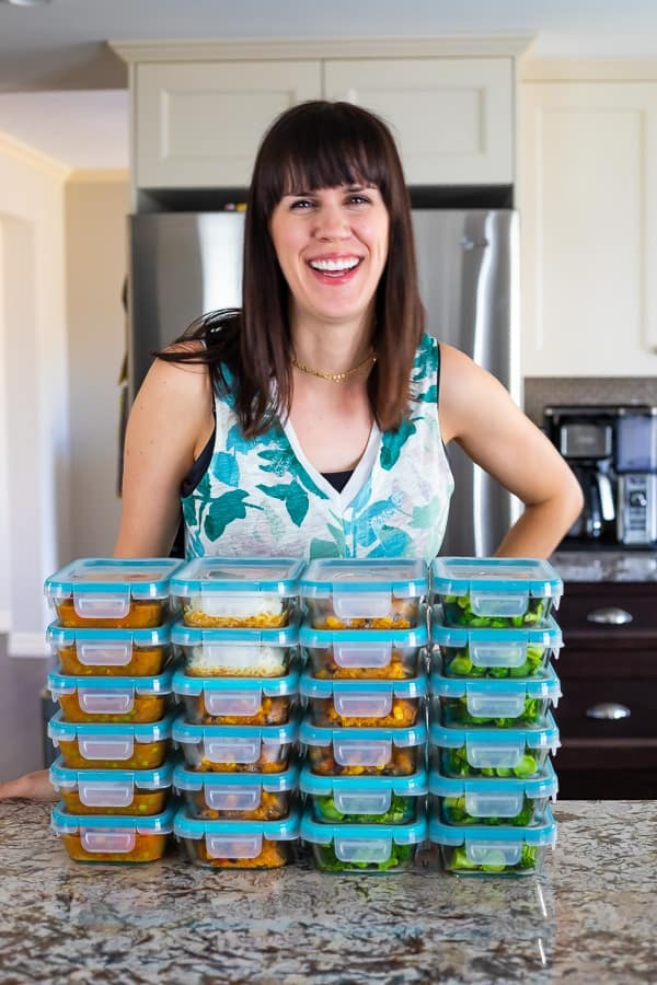 Denise standing behind a stack of glass meal prep containers filled with food