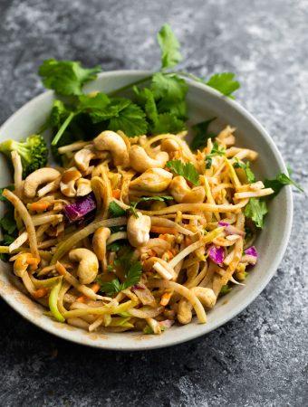 Crunchy rainbow Thai salad in gray bowl with peanuts and cilantro