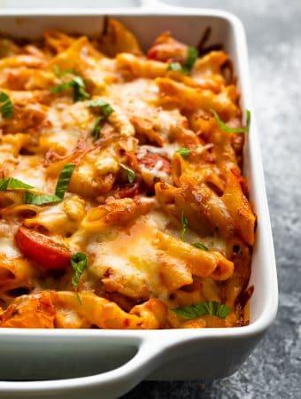 Close up shot of chicken caprese pasta bake in white casserole dish