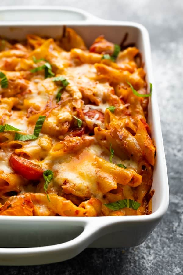 chicken caprese pasta in white baking dish
