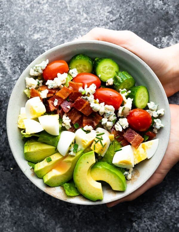 hands holding a gray bowl filled with cobb salad