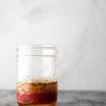 A glass mason jar filled with Greek salad dressing