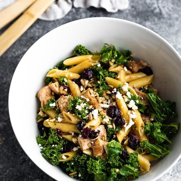 A large white bowl filled with kale chicken pasta salad with wood tongs in the background