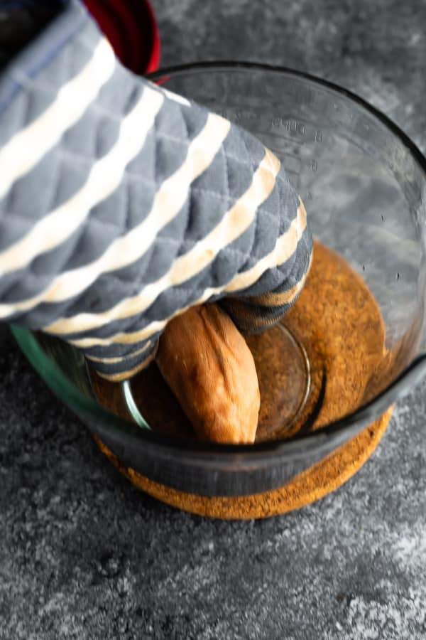 squeezing baked sweet potato microwave with oven mitt