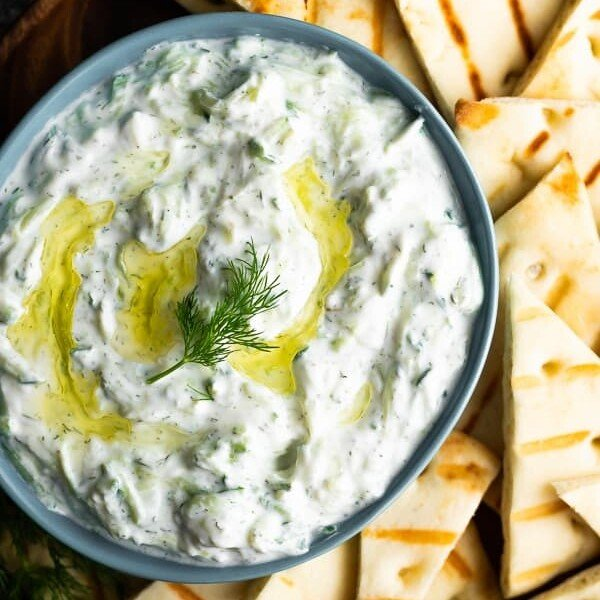Overhead shot of tzatziki sauce in blue bowl with pita slices next to it