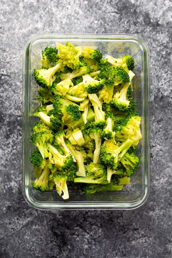 overhead shot of broccoli pieces in glass meal prep container