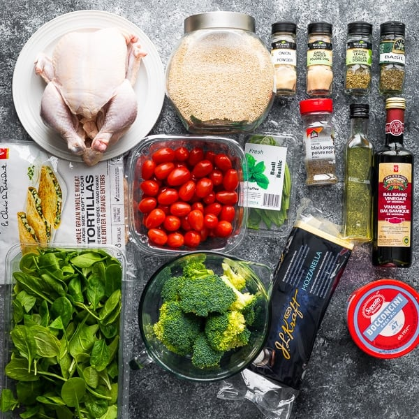 overhead shot of a variety of ingredients for whole chicken meal prep on gray background