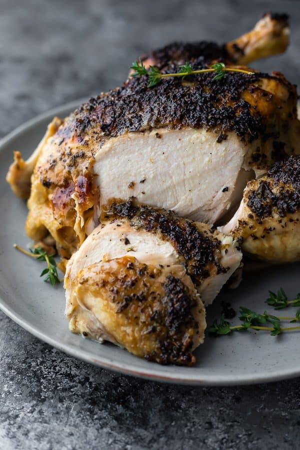 Close up shot of a whole cooked chicken with a few slices off on a gray plate with fresh thyme